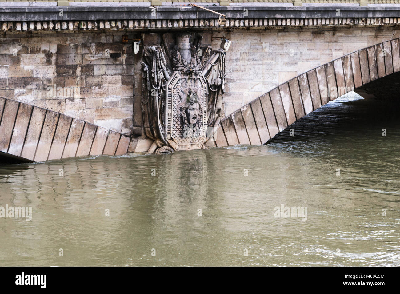 Partially submerged stone relief of militaristic medusa head in coat of arms on Le pont des Invalides in Paris during - Stock Image