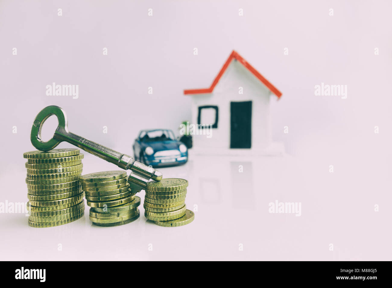 Key on top of a stack of coins with a blurred house and car on the background: real estate, property investment, - Stock Image