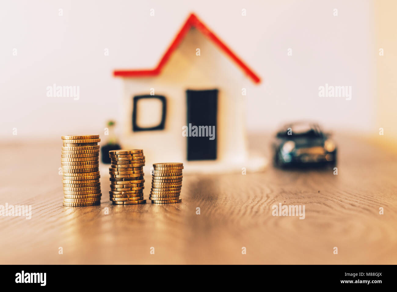 Coins stacked on top of a wooden table, with a blurred house and car on the background: real estate, property investment, - Stock Image