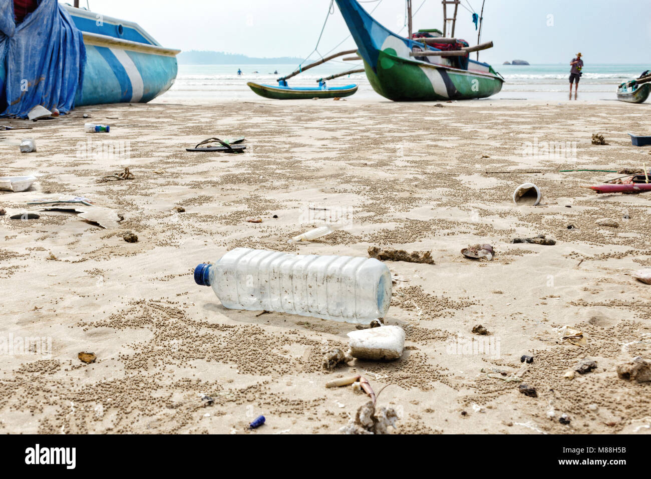 Close up empty used plastic bottle and other waste thrown out at the sea beach on background is fishing boats. - Stock Image