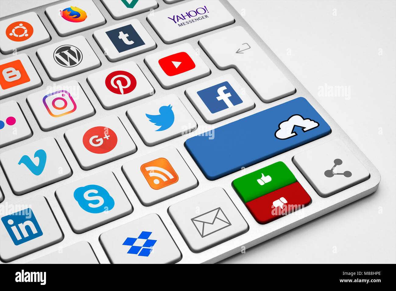 Conceptual keyboard with internet, communication and social media company logotypes illustrating the contemporary - Stock Image