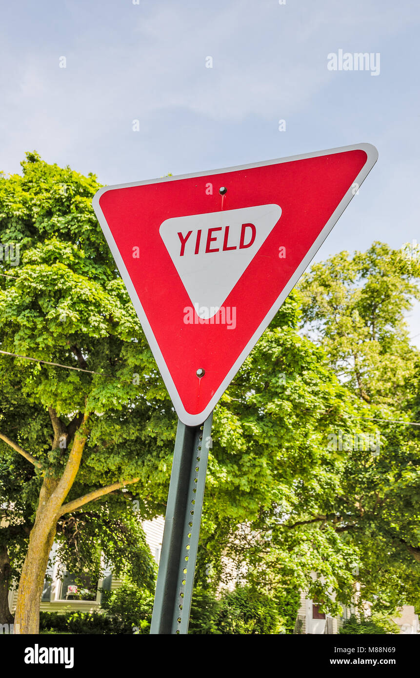 Red and white triangular sign letting motorists know they have to yield the right of way - Stock Image