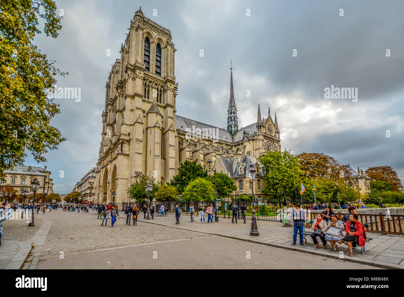 The gothic Notre Dame Cathedral on ile de la cite in Paris France with tourists and clouds in autumn, taken from - Stock Image