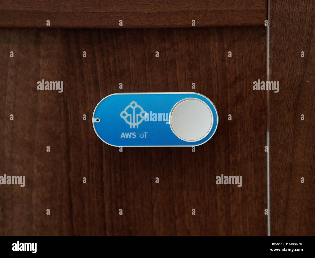 Amazon AWS Dash button - connected IoT device for automatic tasks or purchases. Shown on a wooden door. - Stock Image