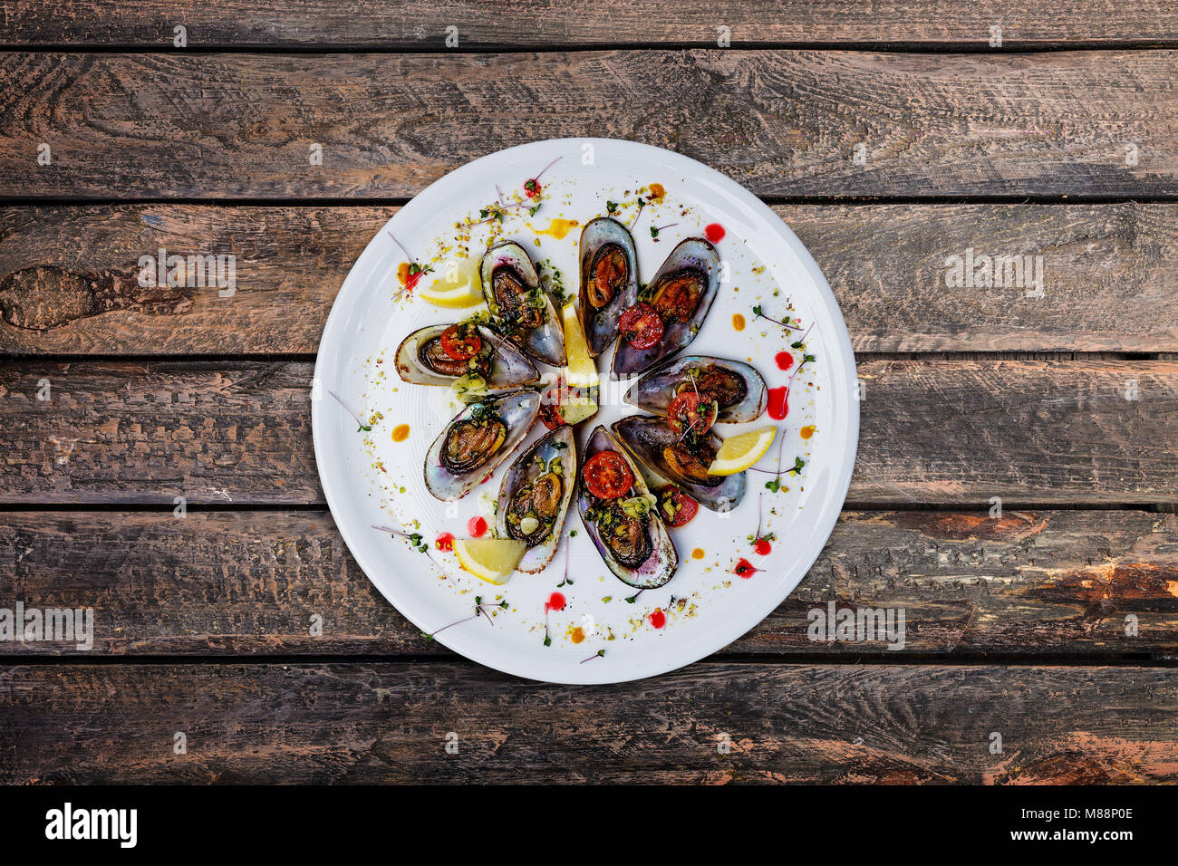 Plate of mussels in garlic sauce. - Stock Image