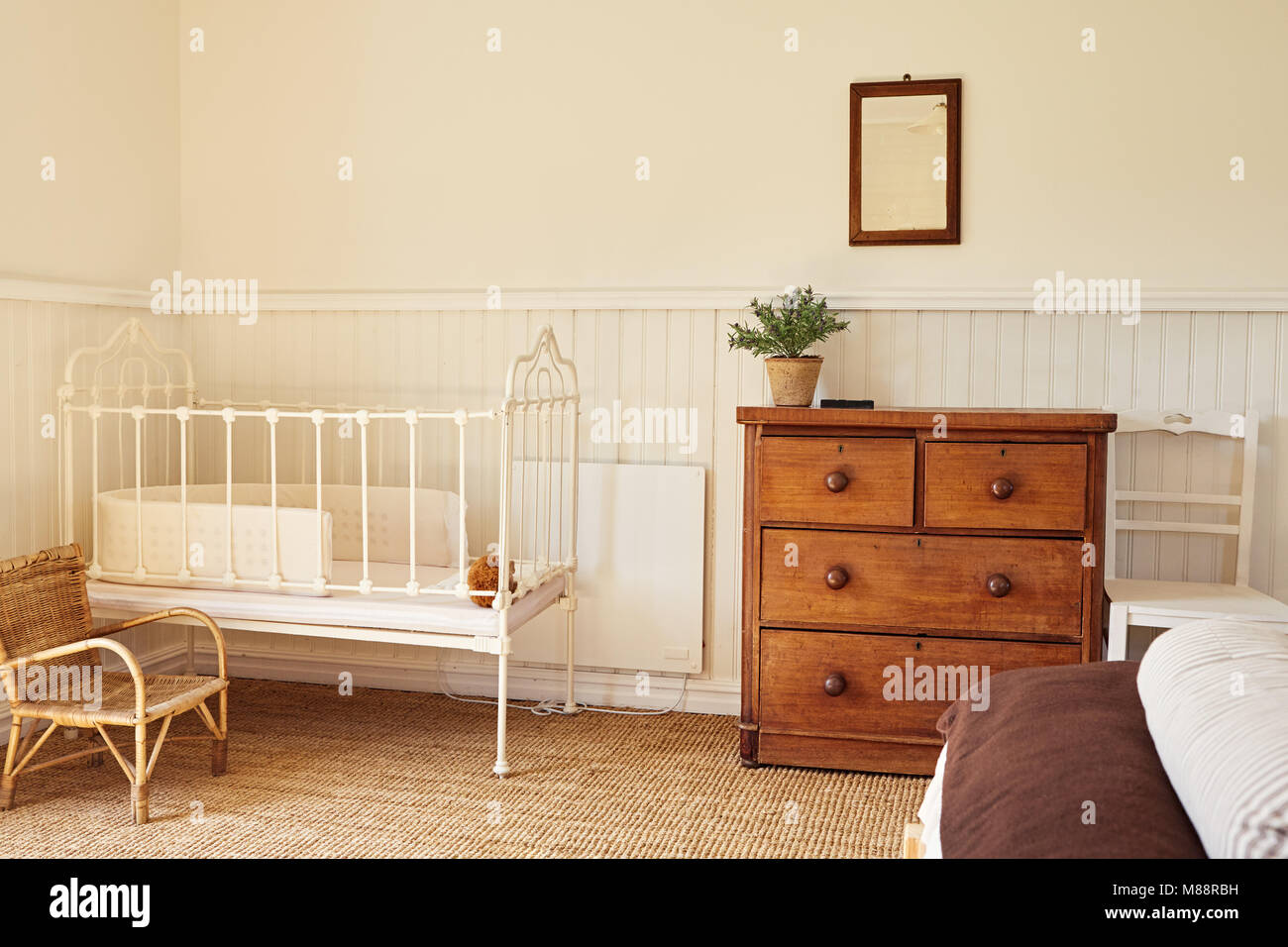 Interior of a bright master bedroom with a bed and baby\'s cot in a ...