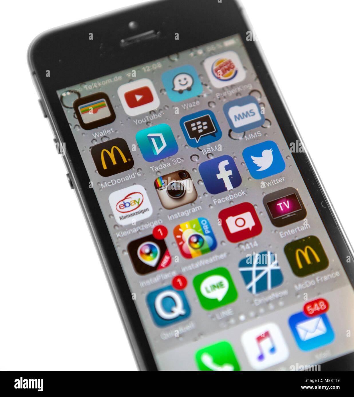 Ein eingeschaltetes Smartohone des Typs Apple iPhone 5s in grau/Schwarz. Auf dem Display sind die einzelnen Apps - Stock Image