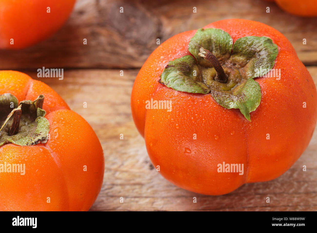 Fresh ripe persimmon with water drops. Selective focus - Stock Image