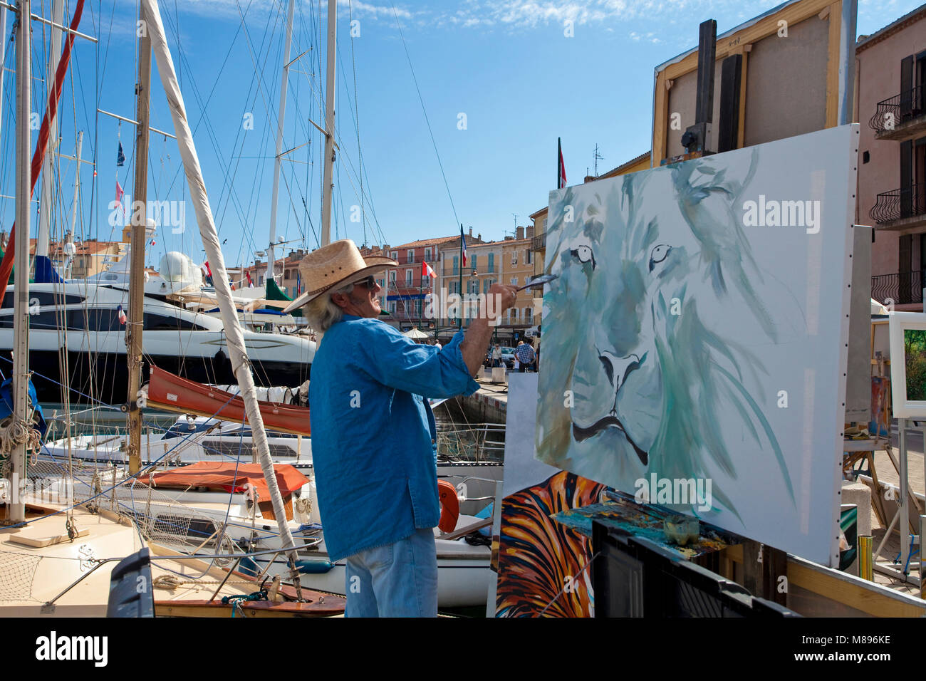 Painter at work, strolling promenade at harbour of Saint-Tropez, french riviera, South France, Cote d'Azur, - Stock Image