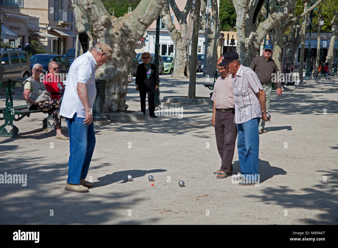 Local men playing Boule (Pétanque) at Place des Lices, a popular game, old town of Saint-Tropez, french riviera, - Stock Image