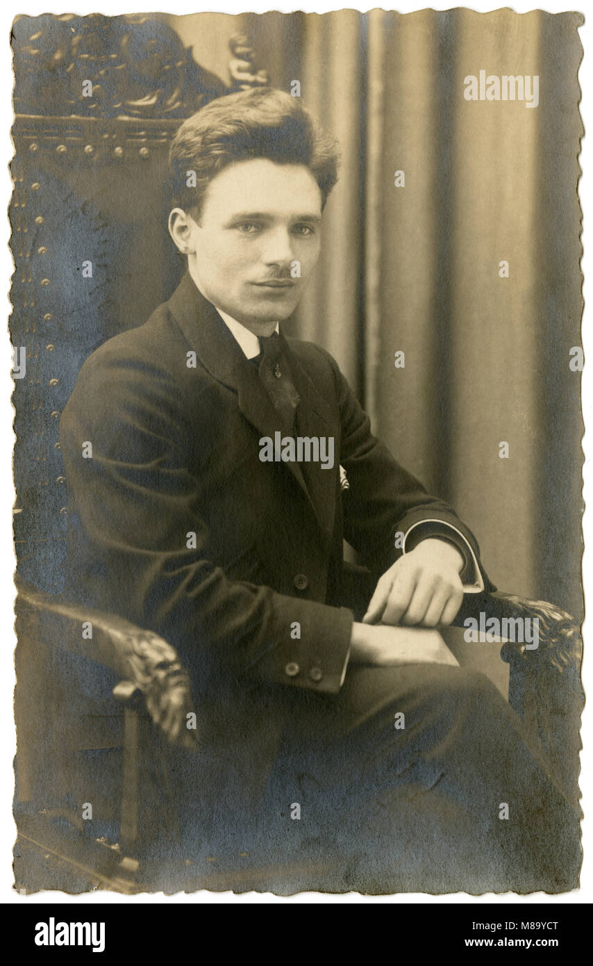 Antique c1920 photograph, 25-year-old man in a fancy library chair. SOURCE: ORIGINAL PHOTOGRAPH. - Stock Image