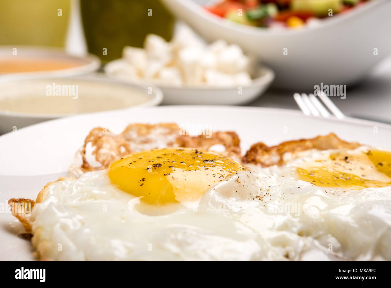 Traditional Israeli Breakfast with two fried eggs, yellow cheese, salad, a fresh roll and a cup of cappuccino. Closeup - Stock Image