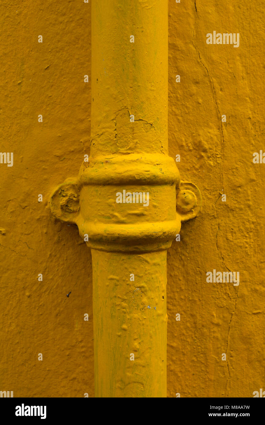 Yellow painted drainpipe and wall - Stock Image