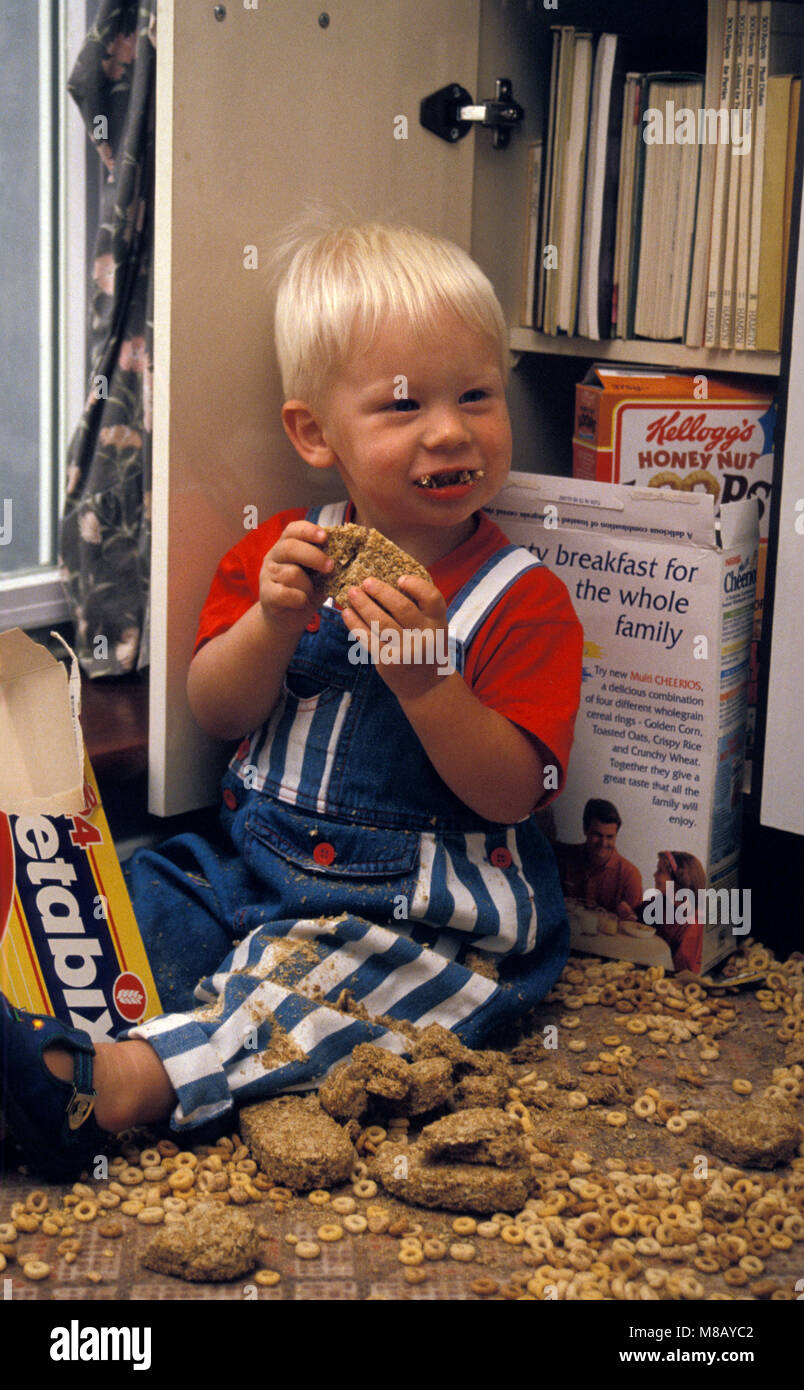 mischievous toddler tipping out cereal boxes all over kitchen floor - Stock Image