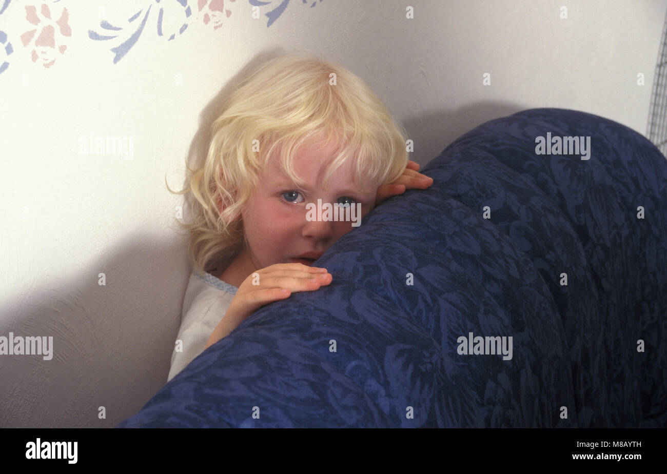 tearful little girl hiding behind sofa - Stock Image