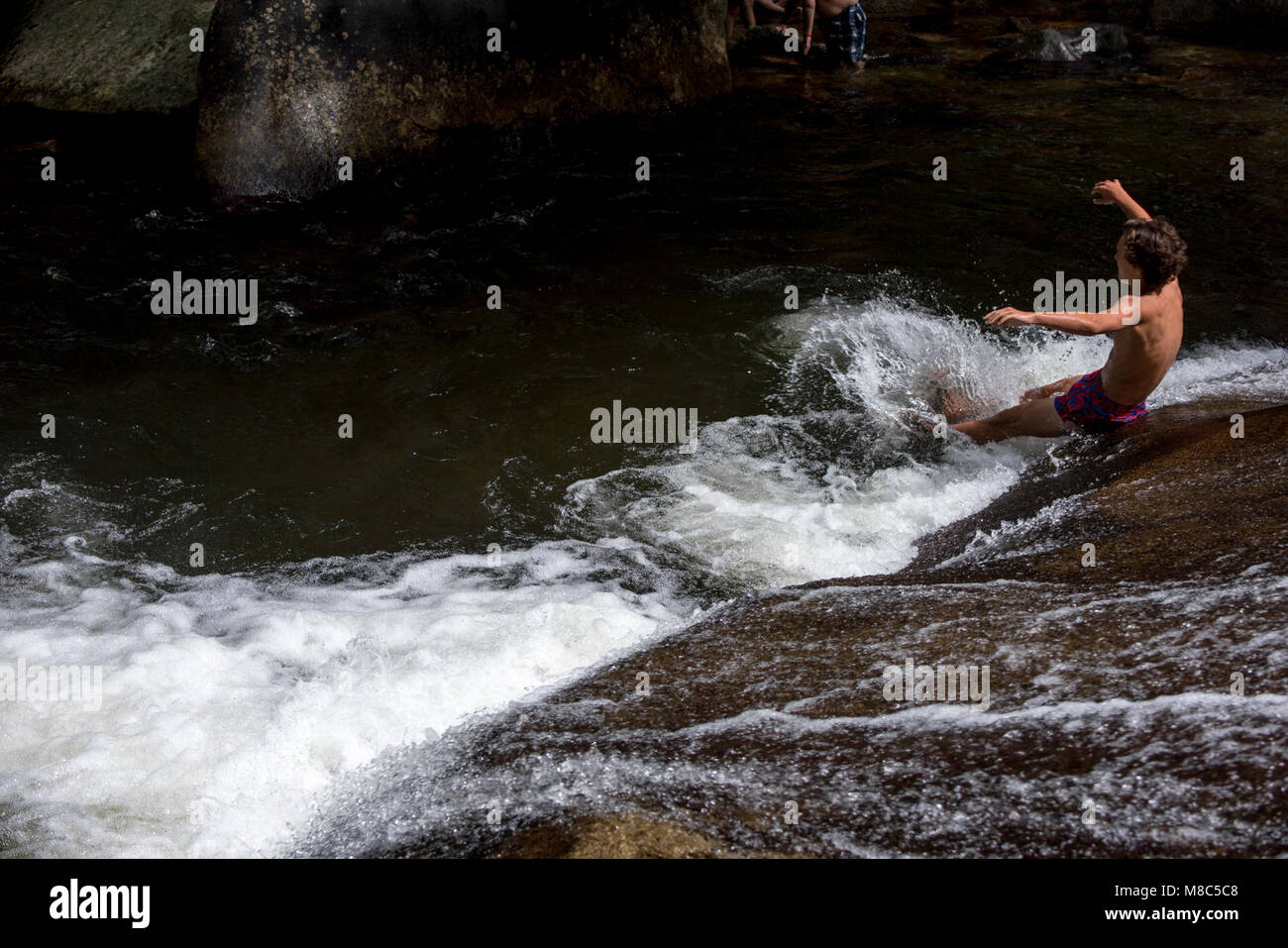 A man slides down the famous Sliding Rock in Pisgah National Forest, NC.    Sliding Rock is a 60-foot slippery cascade - Stock Image