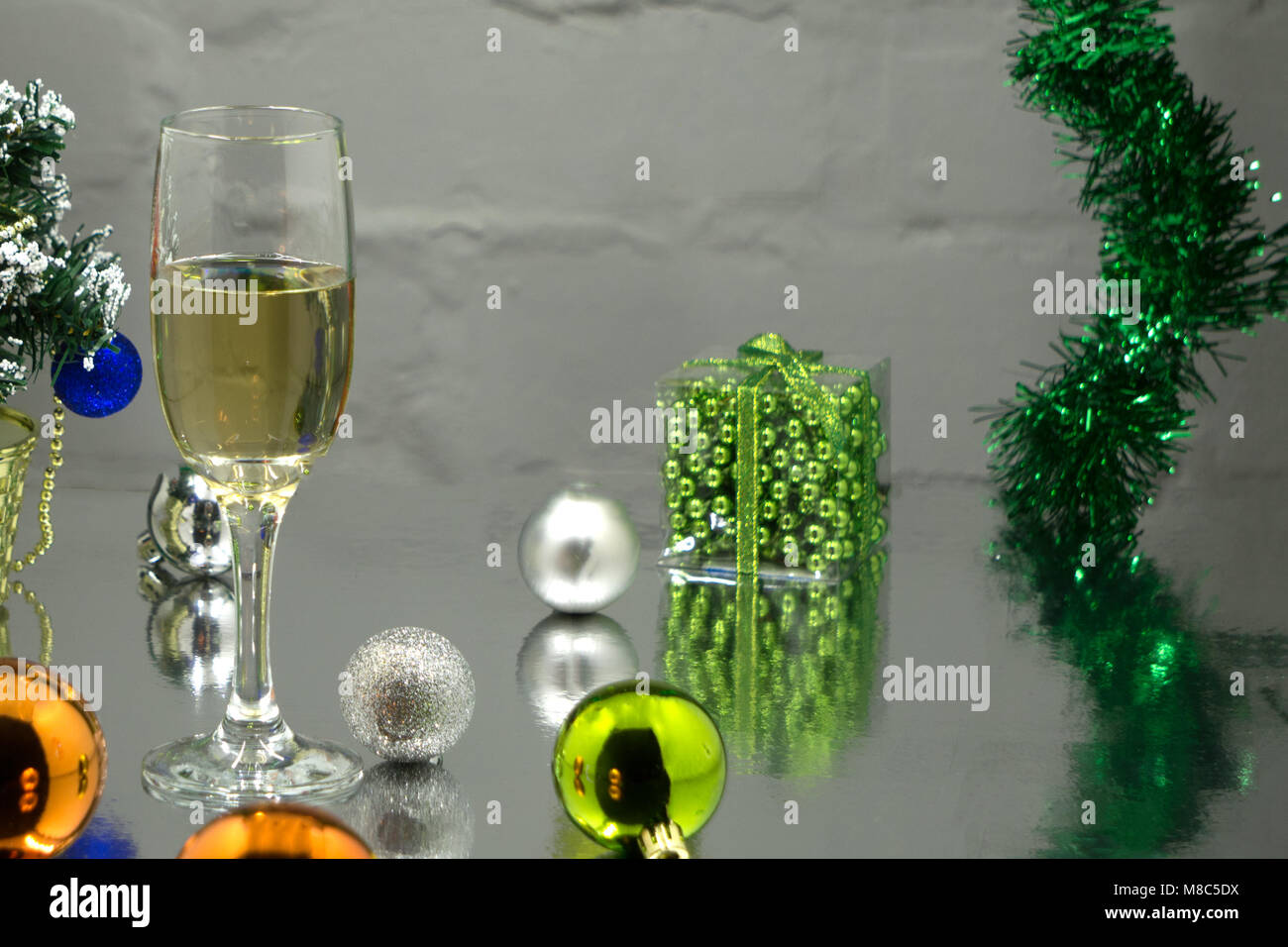 Gift boxes with champagne flutes against gray background - Stock Image