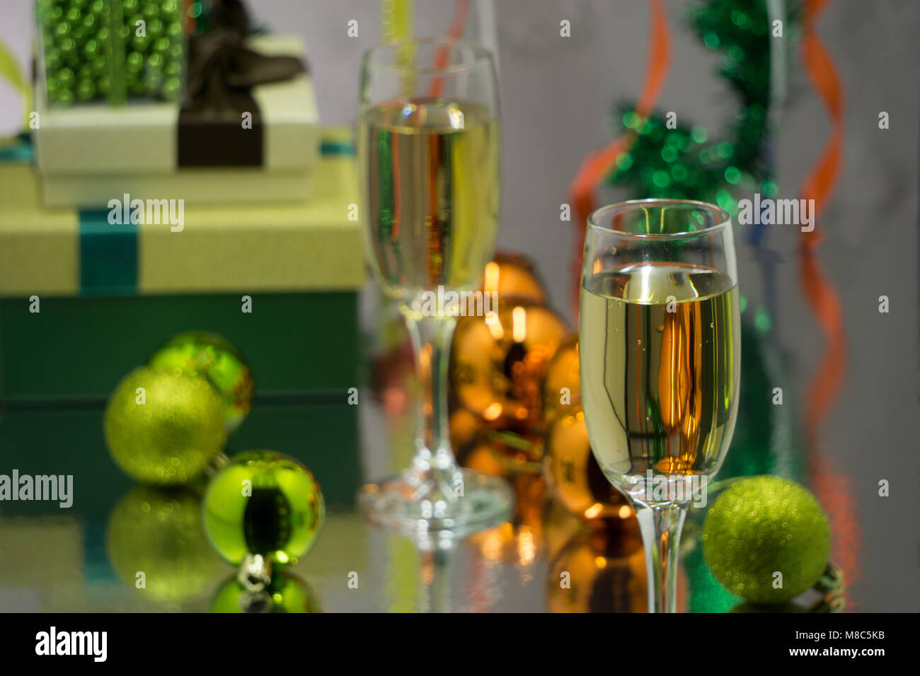 Two champagne glasses and christmas basket bottle, gifts with red satin ribbon, apples candy canes, pine cones branches, Stock Photo