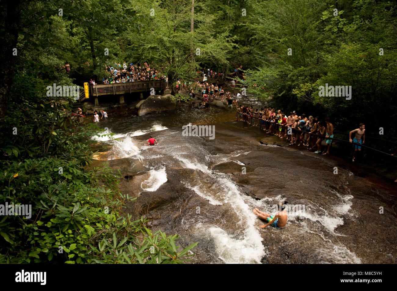 Kids slide down the Sliding Rock in Pisgah National Forest, NC.  Sliding Rock is a 60-foot slippery cascade into - Stock Image