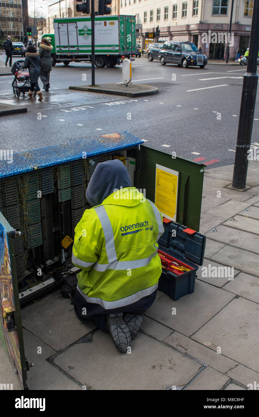 A Bt Or Telecommunications Engineer Technician Working In Large Wiring Openreach Box Exchange Roadside Cabinet Connecting Wires Cutting Off Services Fixing