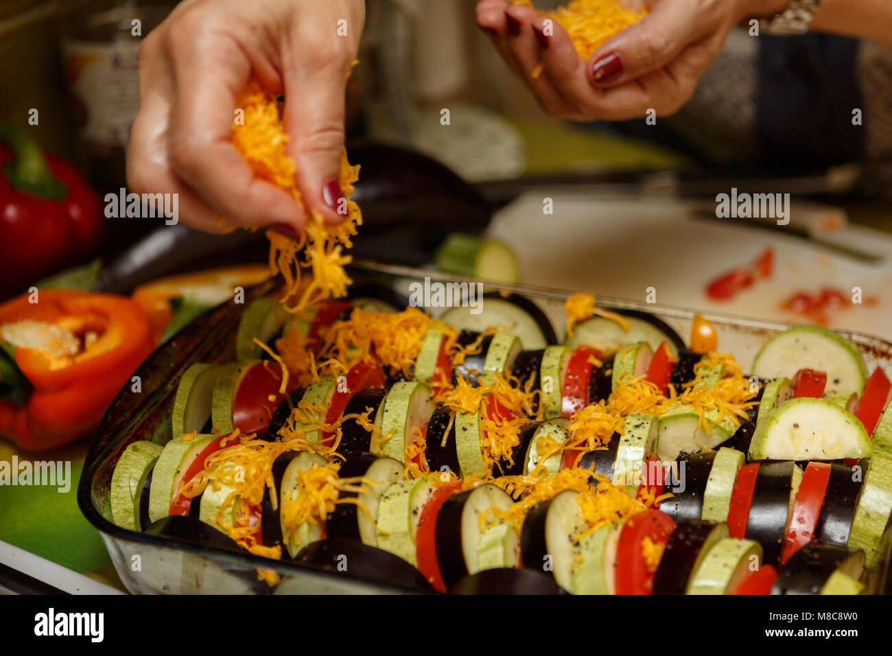 Vegetable ratatouille during cooking. Female hands sprinkle cheese Cheder stacked rows of beautiful vegetables. - Stock Image