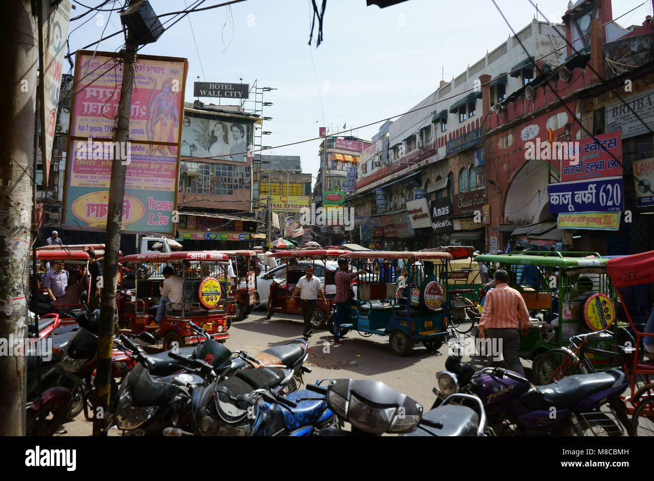 Townsquare filled with parked cars, rikshas, motorcycles in