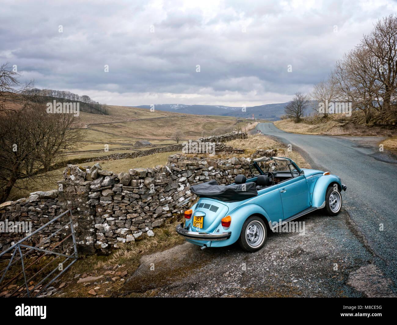 1979 VW Super Beetle cabriolet driving in Yorkshire Dales National Park UK - Stock Image
