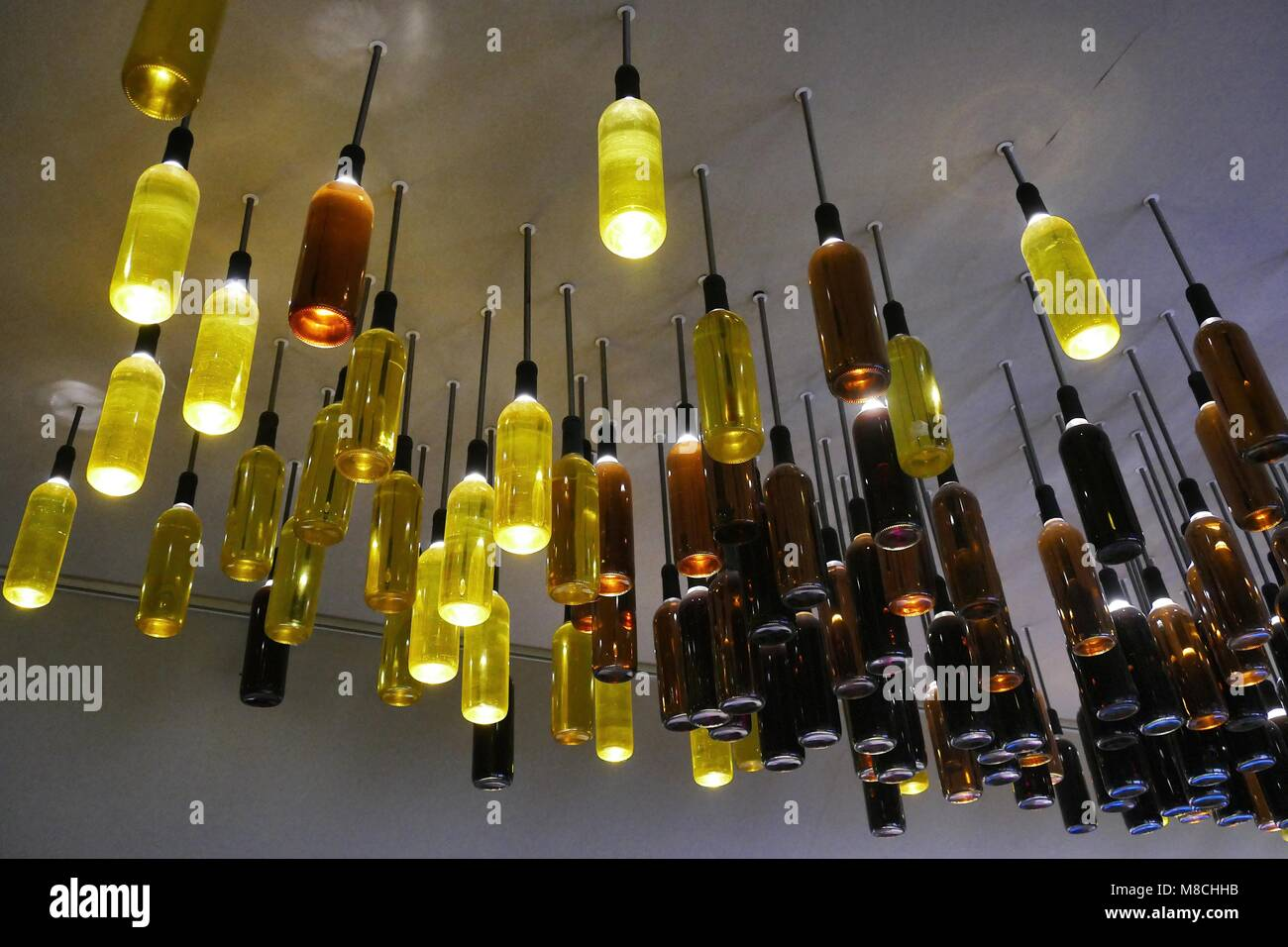 Creative reuse of wine bottles as lamps installed on the ceiling - Stock Image
