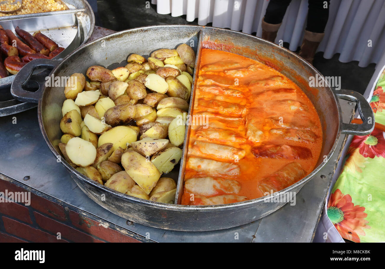 Street fast food - stuffed cabbage with mincemeat and boiled potato in big fried pan. Spring sunny fair day outdoor - Stock Image