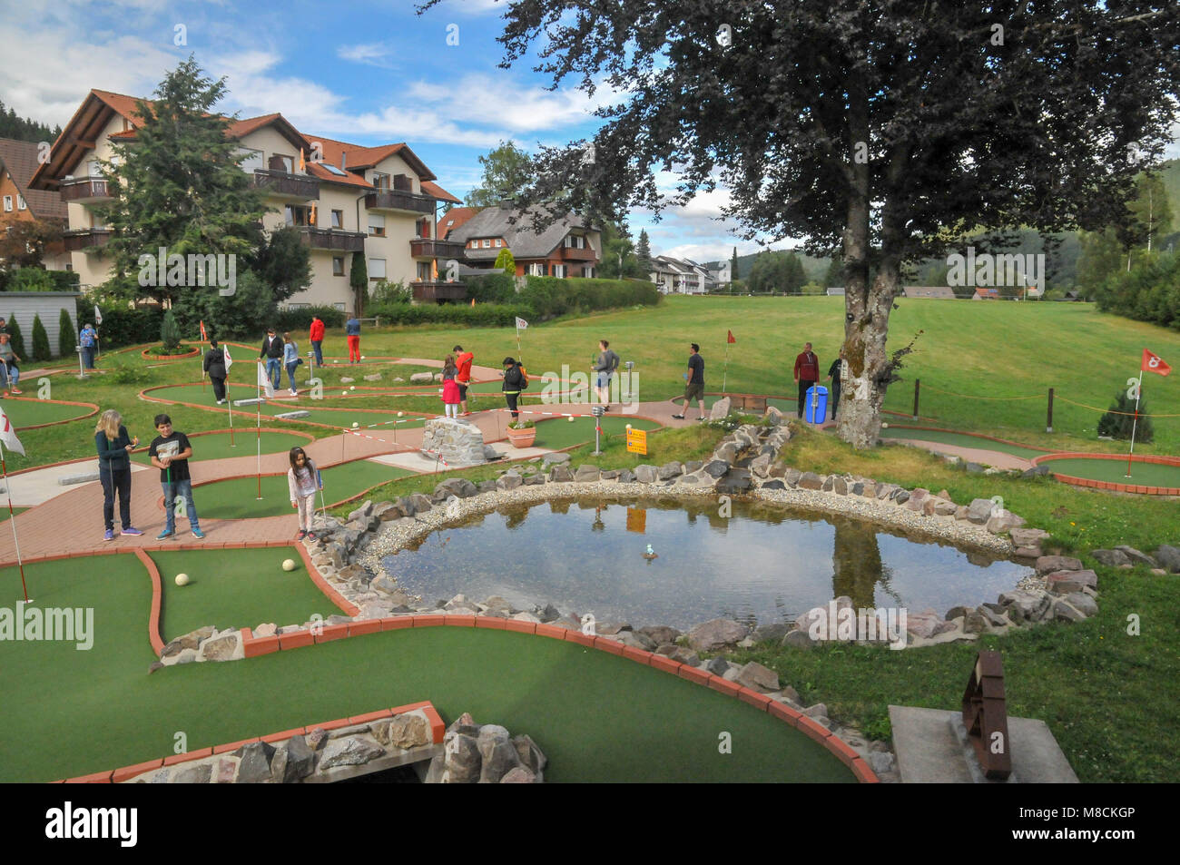 Families putting on a mini golf or putting course Stock Photo