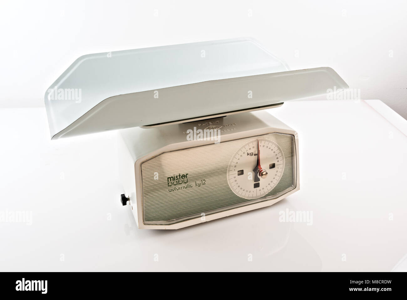 vintage kitchen scales on a white background with a newborn weighing plate 2 - Stock Image