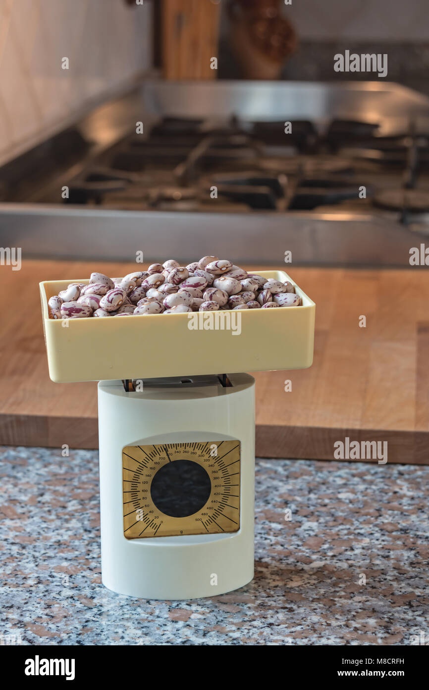 beige vintage kitchen scale on marble top - Stock Image