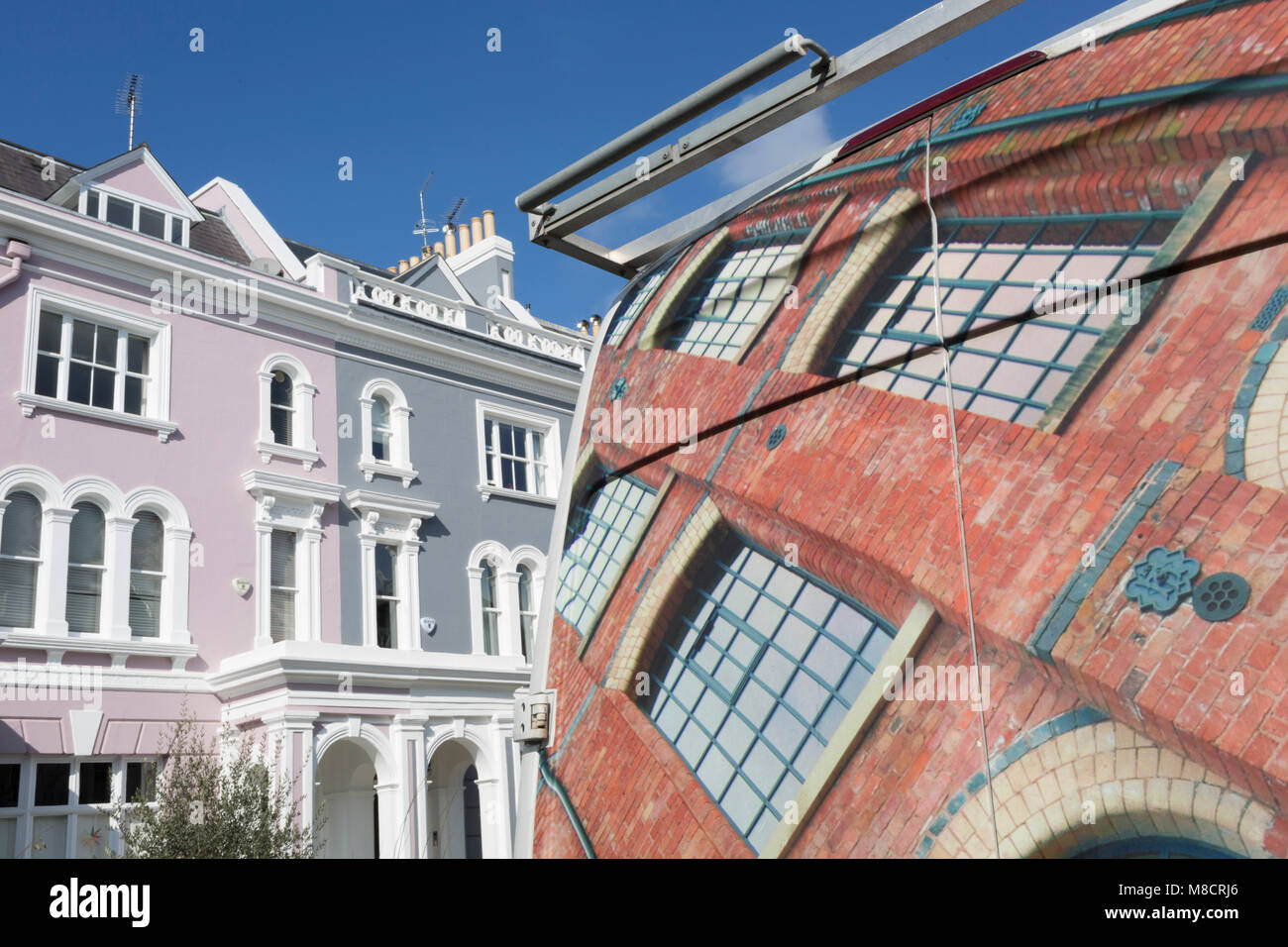 The design on the rear doors of a bespoke window company's van and Victorian houses along Elgin Crescent W11 in Stock Photo