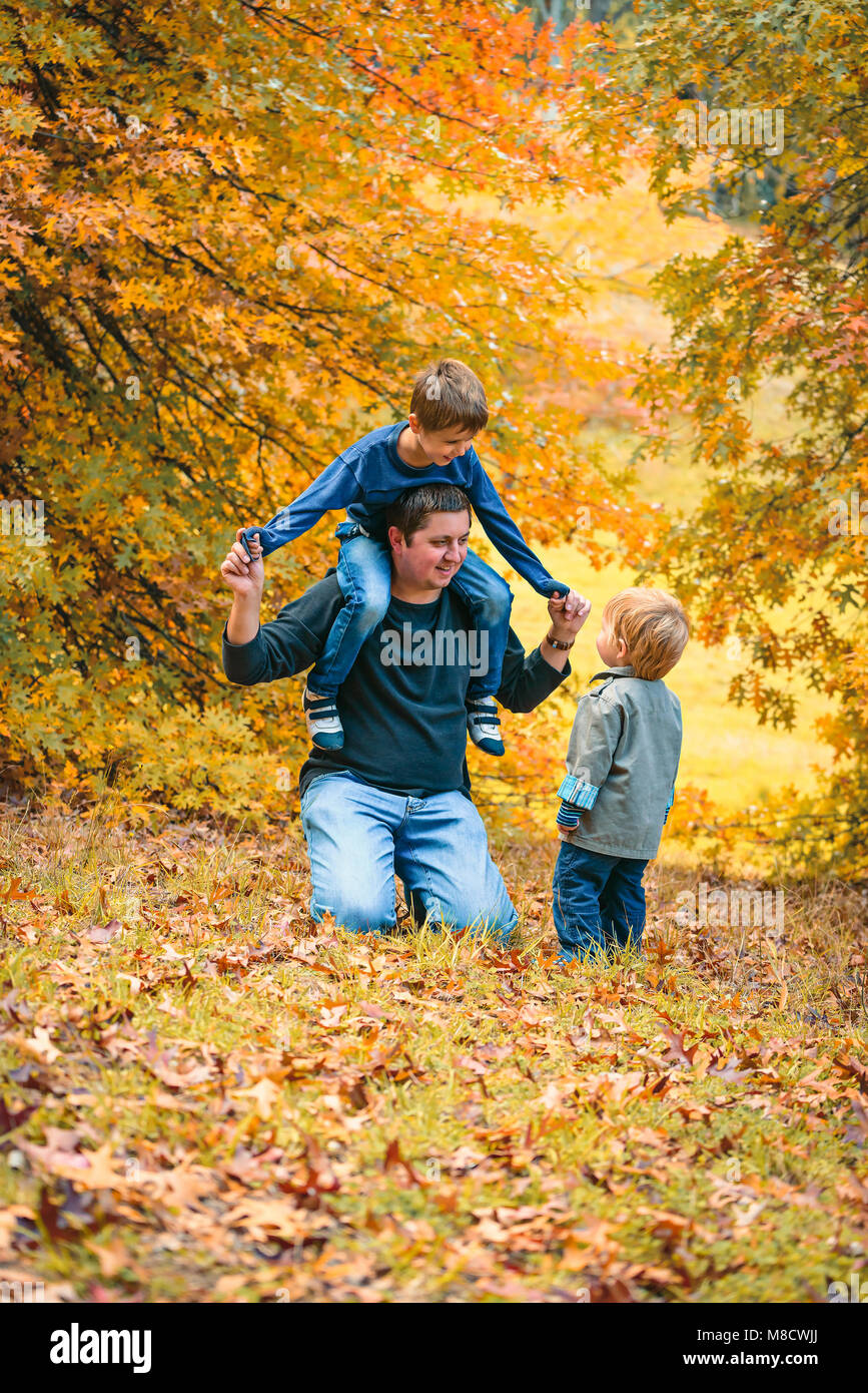 Father having fun with kids in the autumn park - Stock Image