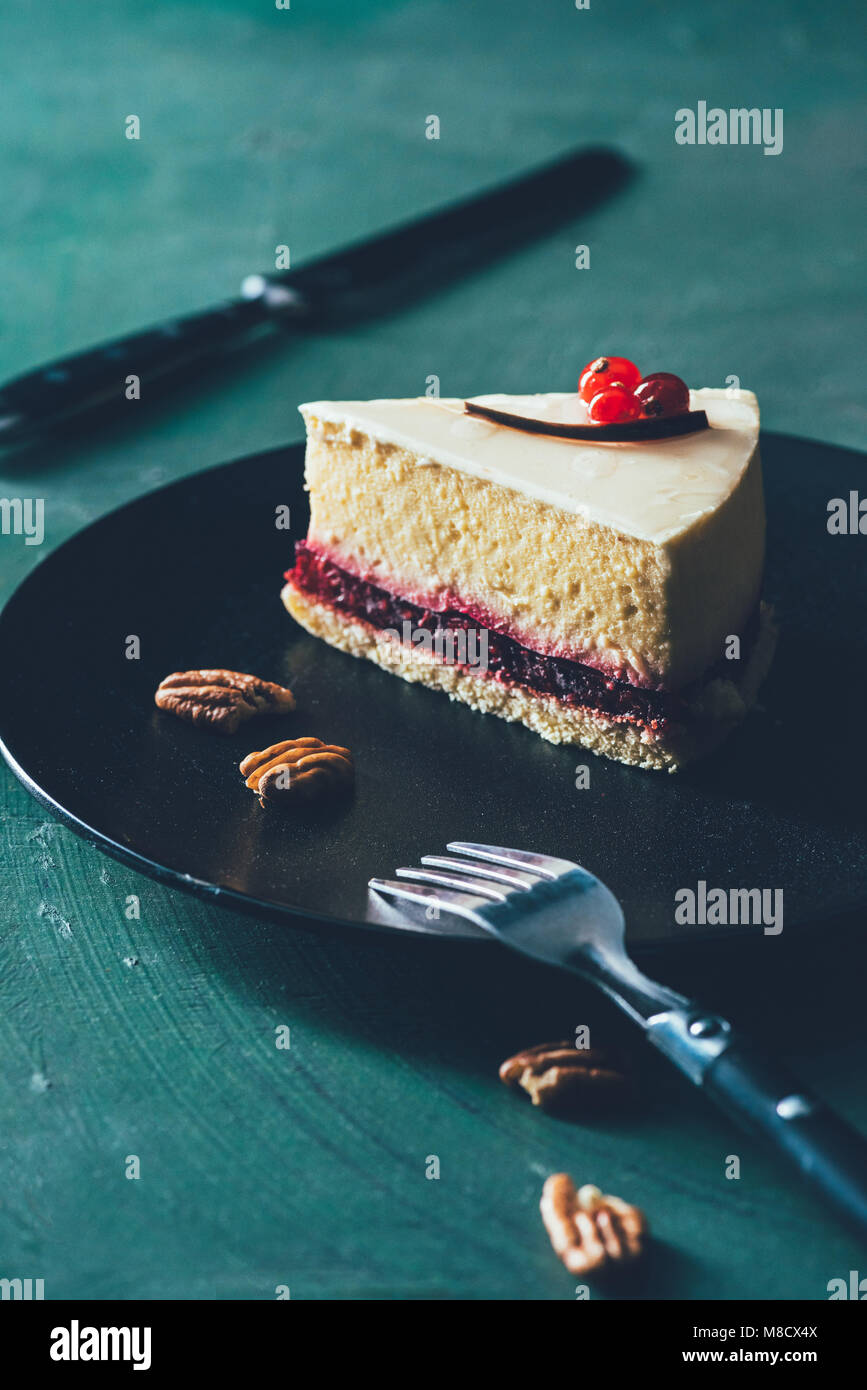 close up view of piece of cake on plate with hazelnuts and fork - Stock Image
