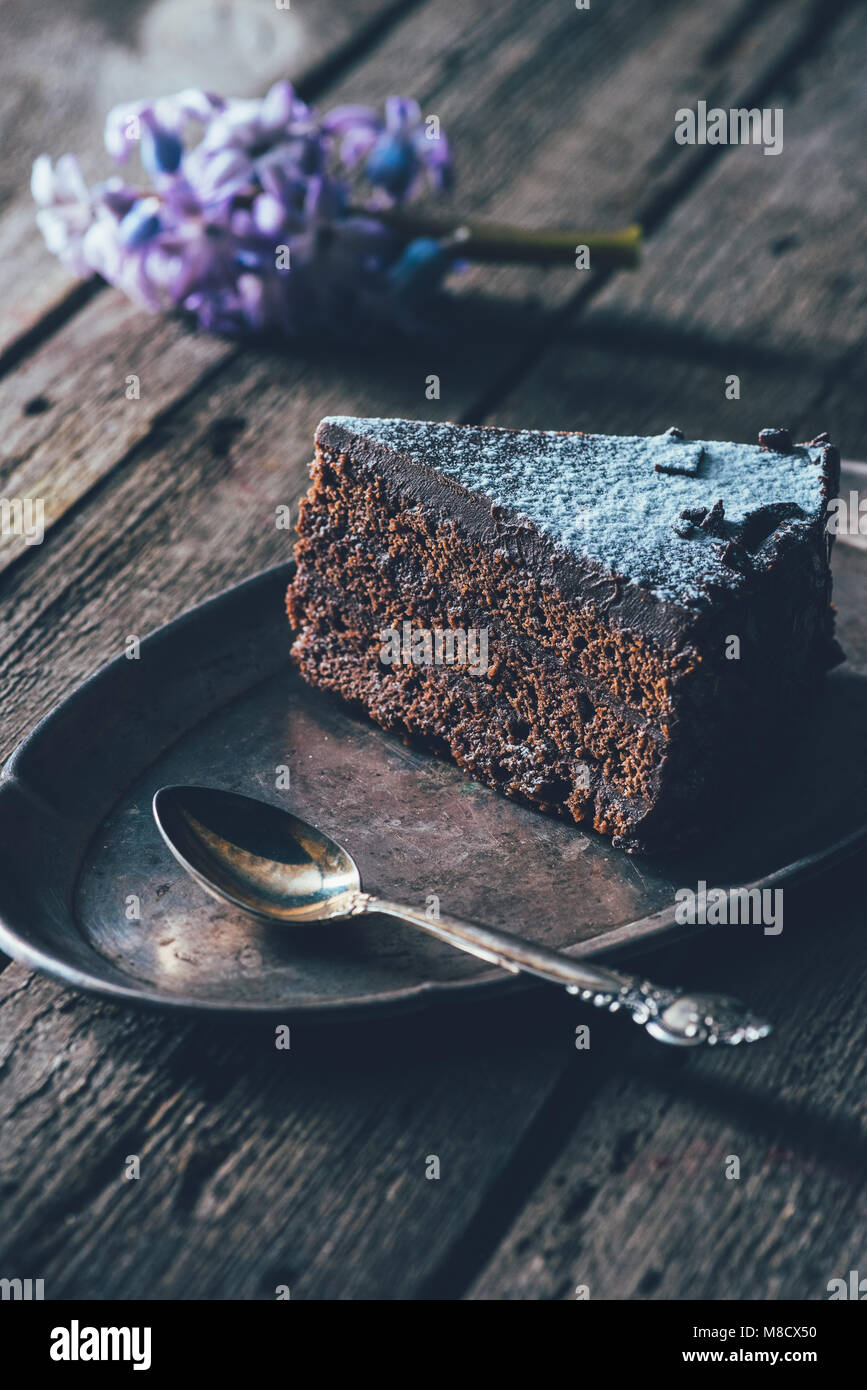 close up view of piece of homemade cake on metal plate on wooden tabletop - Stock Image