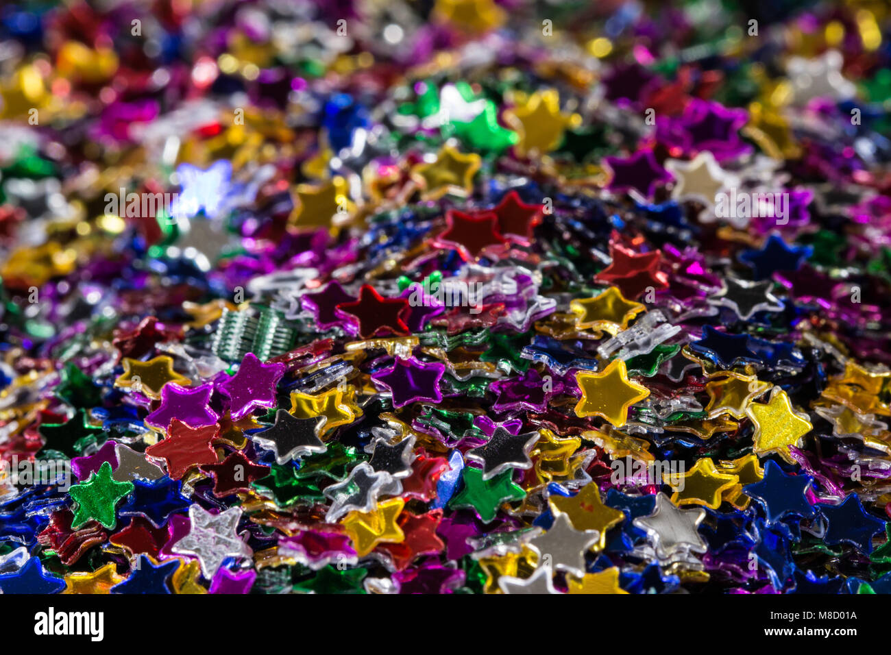 A mound of Colourful glittering festive stars, studio image - Stock Image