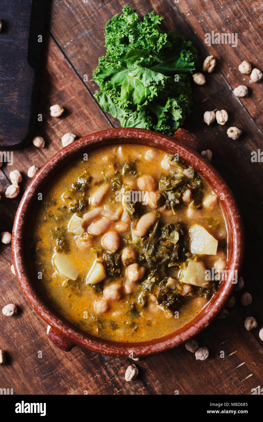 high angle view of an earthenware bowl with kale stew with potatoes and chickpeas, on a rustic wooden table sprinkled - Stock Image