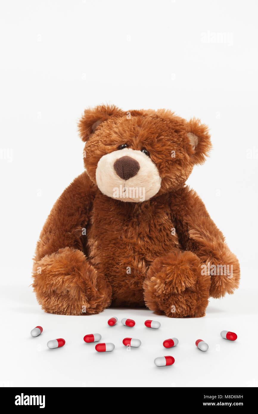 Sad stuffed animal with pills - Stock Image
