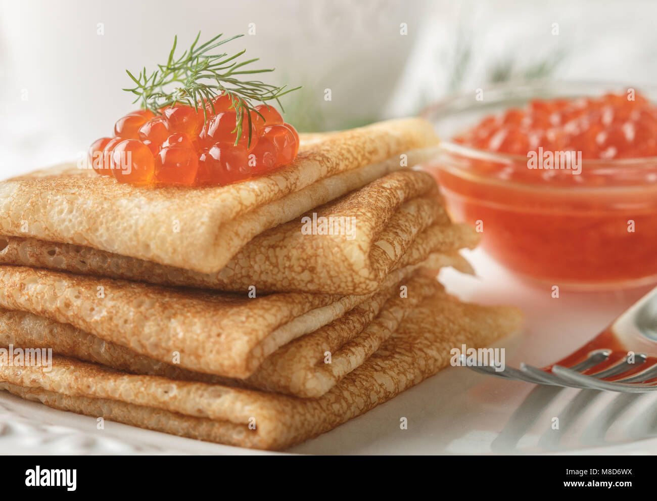 Traditional Russian pancakes (blini ) with salmon caviar on a white plate. Selective focus - Stock Image