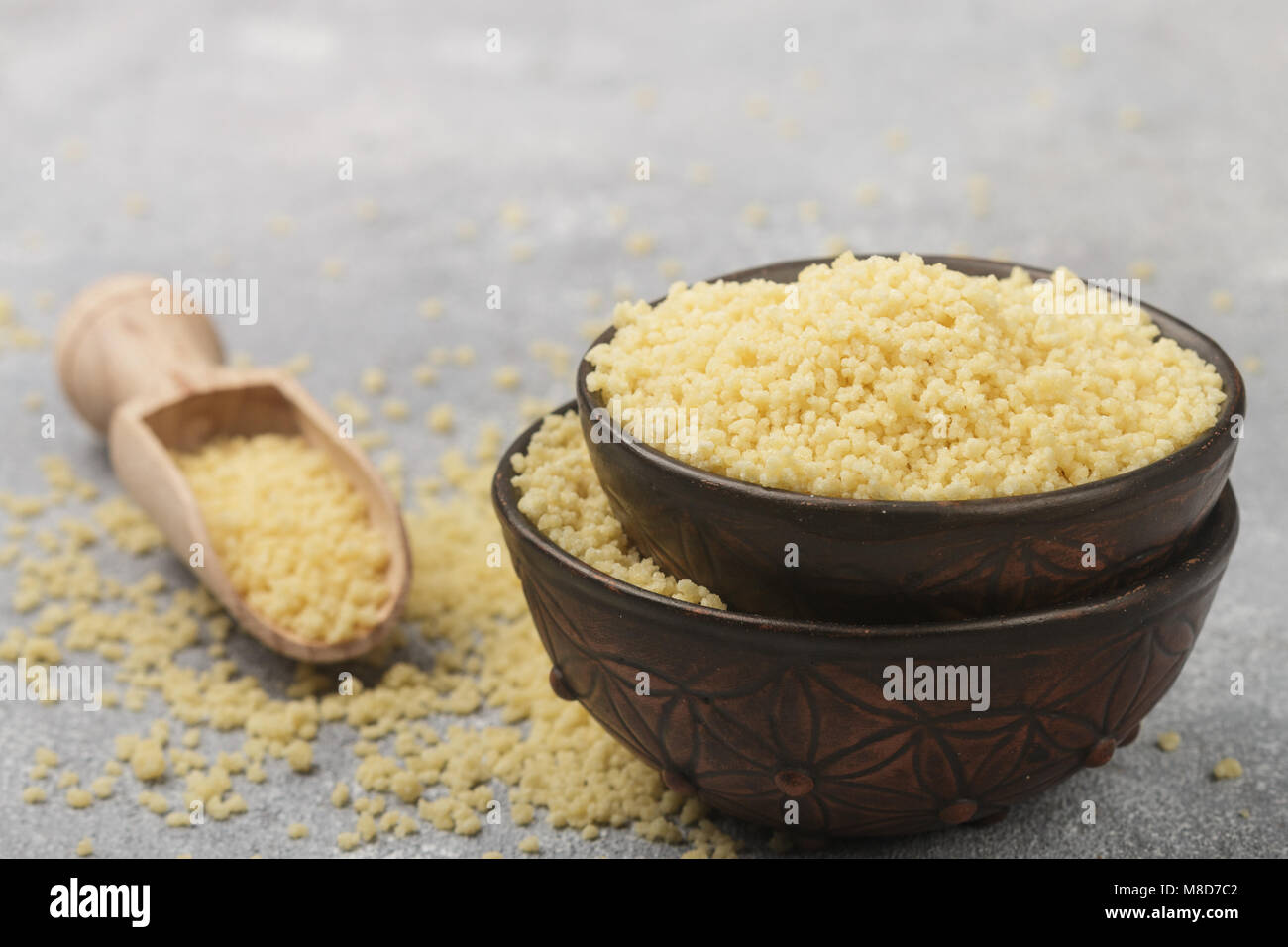 Raw organic couscous in a bowl on the table. Selective focus - Stock Image