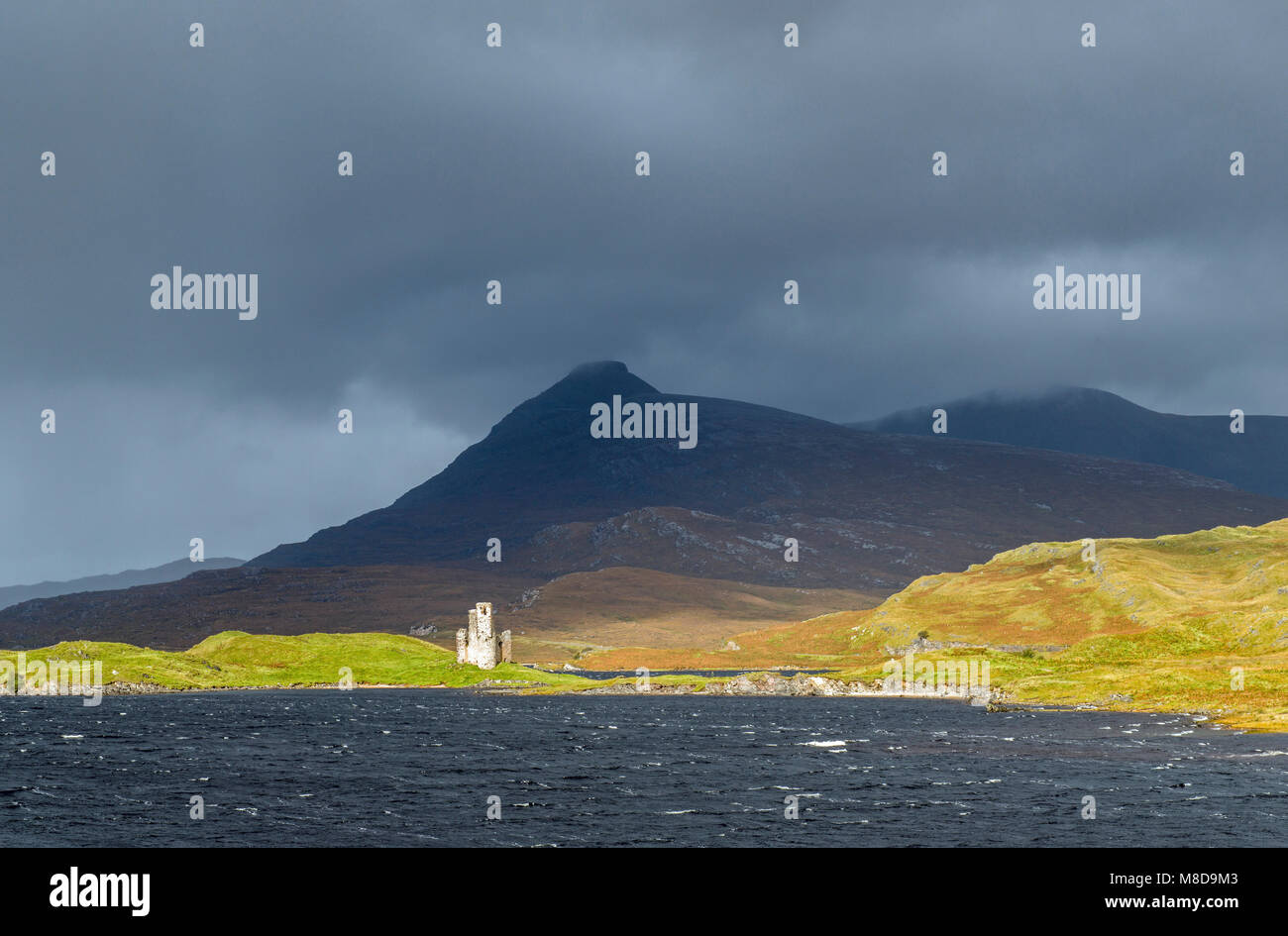 Ardvreck Castle lit up by the sun on the shores of Loch Assynt in the Scottish Highlands in autumn - Stock Image