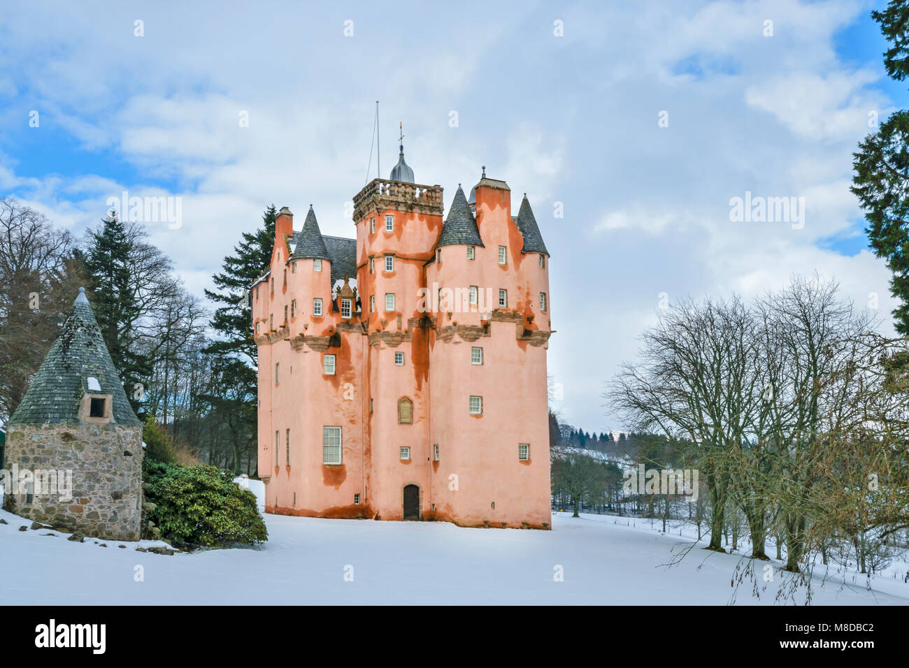 CRAIGIEVAR CASTLE ABERDEENSHIRE SCOTLAND THE PINK TOWER SURROUNDED BY WINTER SNOW  AND EVERGREEN PINE TREES - Stock Image