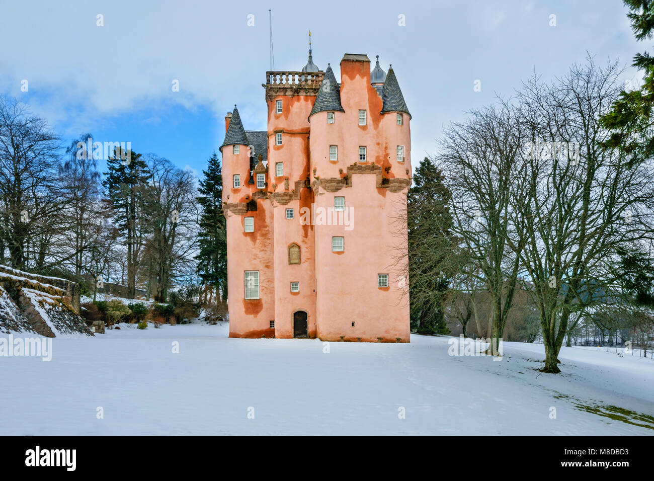 CRAIGIEVAR CASTLE ABERDEENSHIRE SCOTLAND WITH THE PINK TOWER SURROUNDED BY WINTER SNOW  LEAFLESS TREES AND A SMALL - Stock Image