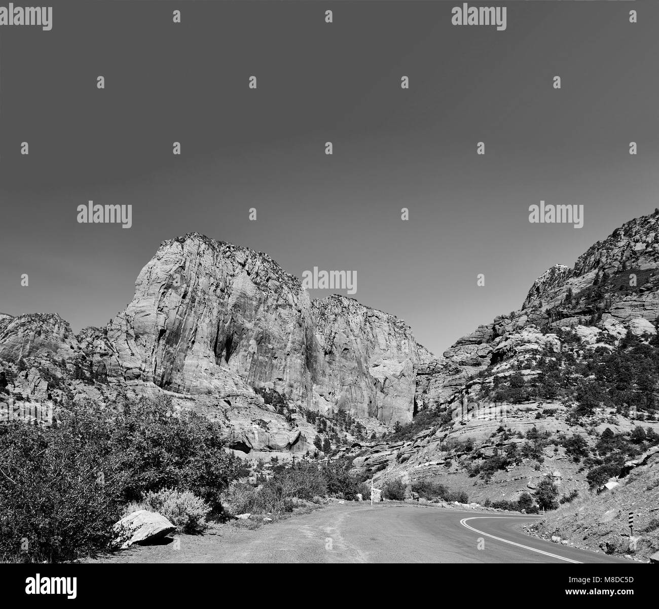 Kolob Canyon in Zion national park, Utah. Mountain peaks, clear sky, trees, road, cliffs. - Stock Image