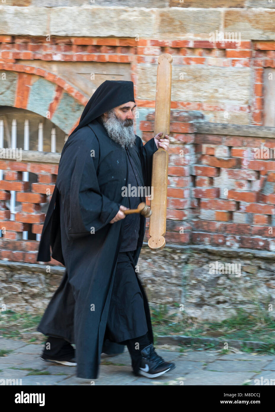 An orthodox monk sounds the call to evening prayer by striking a wooden semantron at the Skete of Saint Andrew at - Stock Image