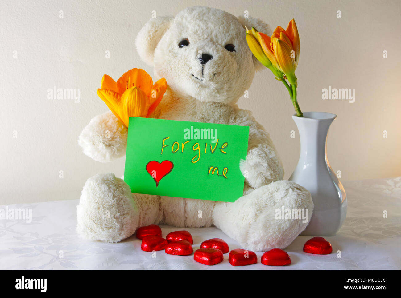 Cute white teddy bear holding agreen sign that says forgive me - Stock Image