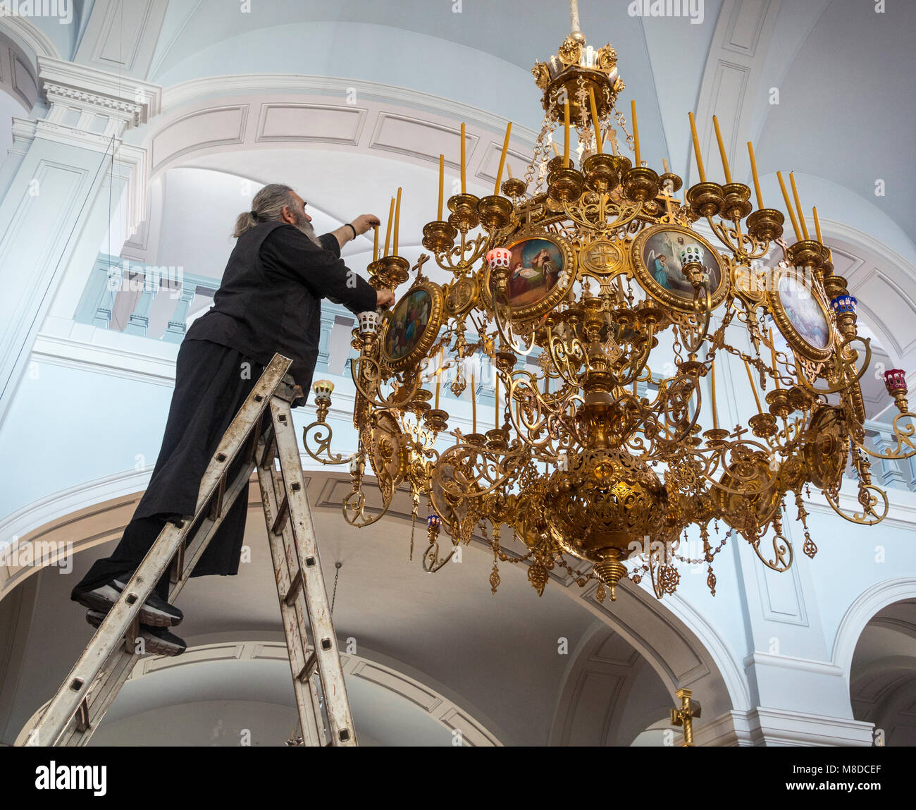 A monk replacing candles in a chandelier in the church at The Skete of Saint Andrew at Karyes on The Athos peninsula, - Stock Image