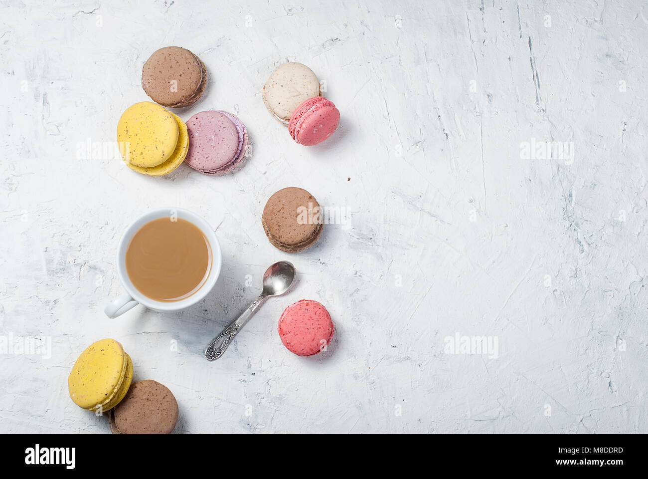 cup of coffee with milk and colorful makaoouns on a light background. Top view. Copy space. - Stock Image