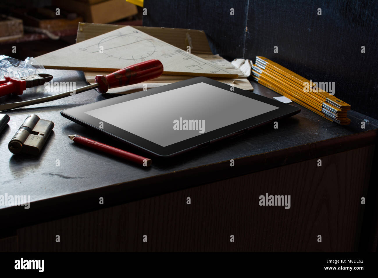 Tablet With Blank Screen On A Dark Cupboard With Tools In A Dirty Basement - Stock Image